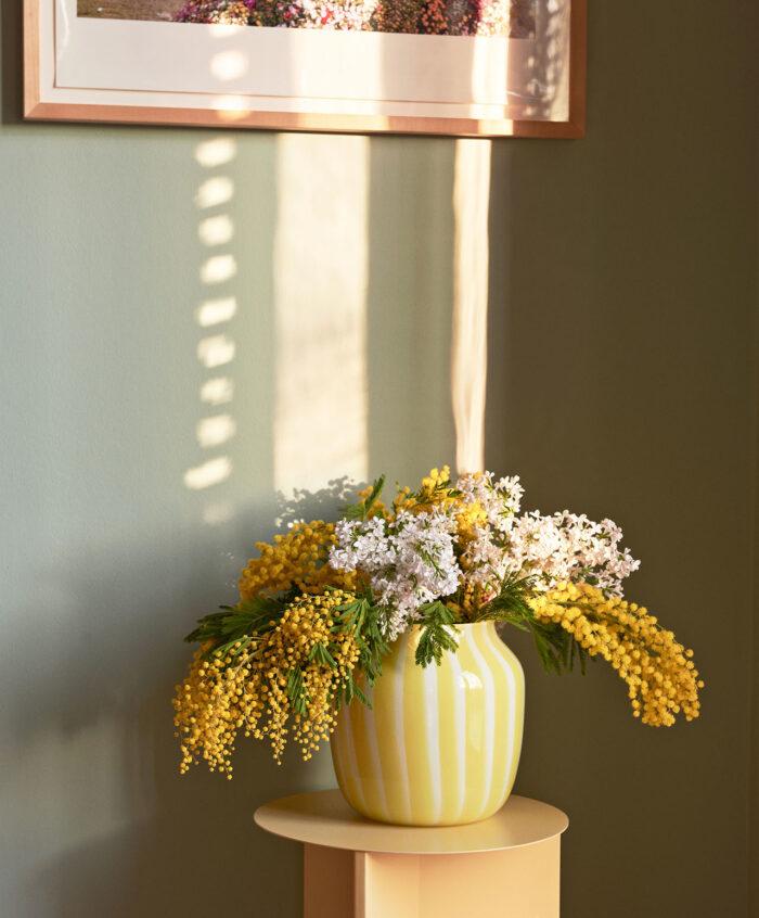 Rayas de moda en amarillo y blanco en un jarrón de heno