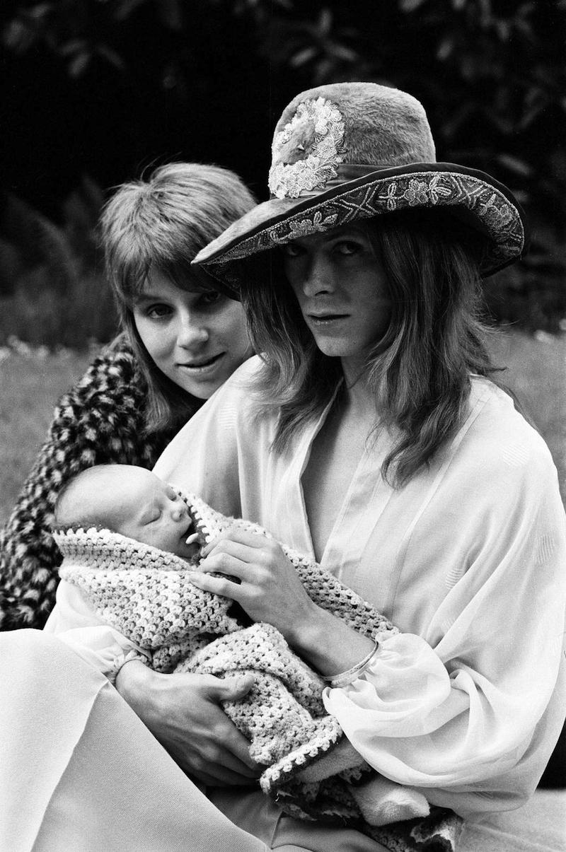 Pop star David Bowie with wife Angie and three week old son Zowie. He is modelling an Oxford Bags dress, Turkish cotton shirt and a felt hat. 29th June 1971.